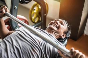 joven asiático haciendo levantamiento de pesas con barra en el club deportivo de gimnasio. deporte y concepto de construcción corporal. concepto de fuerza y entrenamiento muscular. tema divertido y esfuerzo foto
