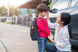 Mom preparing to send her children back to school at car in morning. Education and Back to school concept. Happy family and Loving of people theme photo