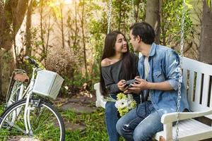 Asian couple having eye contact as romantic moment at bench in natural park with bicycle. People and lifestyles concept for Valentines day and wedding ceremony. Love at first sight theme photo