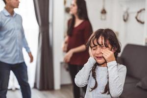 niña llorando porque sus padres se pelean. niña abusada con madre y padre gritando y conflicto de fondo enojado en casa. Escena dramática familiar, concepto de problema de problemas sociales familiares foto