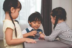 niño luchando por juguetes con sus hermanas. concepto de familia y niños. tema de conflicto y disputa. tu gente en casa foto