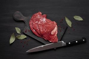 Fresh uncooked meat on wooden board with knife photo