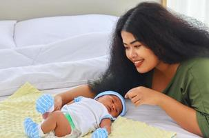 Mother is enjoying playing with her newborn son happily Concept of love and family ties photo