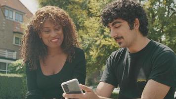El hombre sostiene el teléfono inteligente y habla de él mientras está sentado con la mujer en el parque video