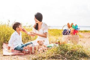 hermosa mamá asiática alimentando bocadillos a su hijo en la pradera cuando hace un picnic. madre e hijo jugando juntos. celebrando el día de la madre y apreciando el concepto. gente de verano y tema de estilo de vida. foto