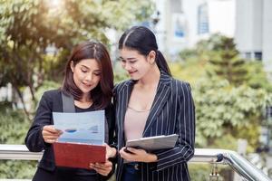 Dos jóvenes empresarias asiáticas que buscan en la carpeta de archivos de documentos para analizar el punto de equilibrio de ganancias o ventas después de la comercialización. Empleados de trabajo en equipo de negocios del concepto de mujeres trabajadoras de estilo de vida foto