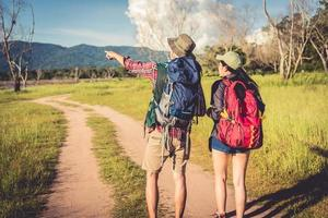 Two people walking on path in meadow field. Male and female traveler looking at attraction view point. Couples adventure at outdoors together. People and lifestyles concept. Trip and camping theme photo