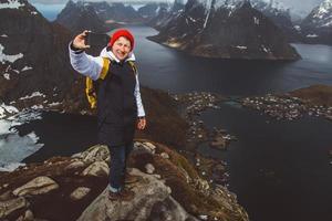 Hombre viajero tomando una foto autorretrato con un smartphone senderismo en la cresta de la montaña en Noruega