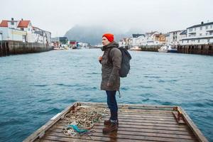 Traveler man with a backpack standing on woode pier on background of fishing houses mountain and lake photo