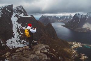 Hombre viajero tomando fotos con un smartphone senderismo en la cresta de la montaña en Noruega