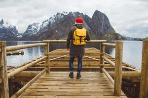 Traveler man with a backpack standing on woode pier on background of mountain and lake photo