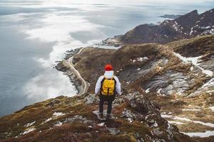 Traveler man with a yellow backpack standing on rocks against background of sea and mountains photo