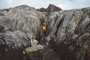 Traveler man with a yellow backpack wearing a red hat standing on the background of the rocks. Travel lifestyle concept. Shoot from the back photo