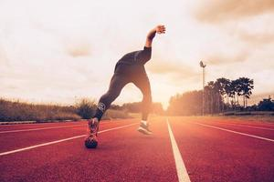 Sunset and Young man running on lane. Success and goal of business concept. Sport athletic and exercise theme photo