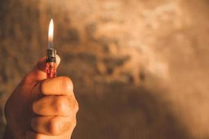 hombre de la mano de cerca con encendedores enciende el fuego sobre la quema de fondo. foto