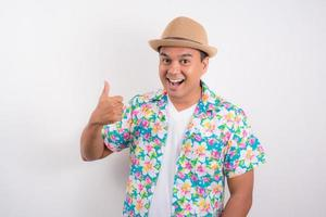 Young asian man wearing summer shirt and showing thumb up for Songkran festival in Thailand. photo