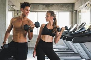 Fitness man and woman holding dumbbell standing posing near treadmill. Muscular couple training at the gym. photo