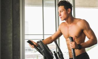 Young man at the gym exercising on the cross trainer machine. Fitness man doing cardio workout program. photo