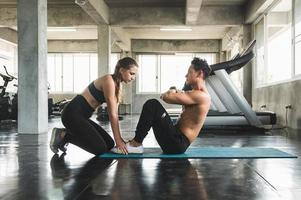 Couple love young fitness man and women workout exercise together. Weight training and cardio program concept. photo