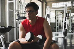 Strong muscular asian man workout in gym doing exercises at biceps.  Weight training concept. photo
