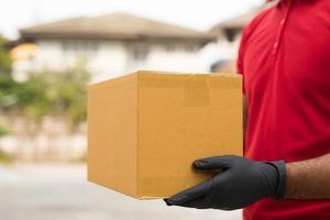 cartero en rojo con uniforme de guante que sostiene el paquete. foto