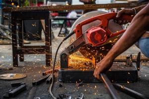 Worker man using machine cutting steel photo