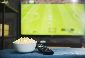 Popcorn and television remote control on football program tv screen background. Watching tv relax concept. photo