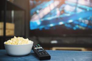 palomitas de maíz y control remoto de la televisión en el fondo de la pantalla del televisor. viendo la televisión relajarse concepto. foto