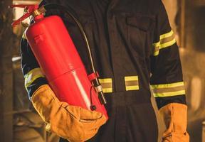 Cerrar mano bombero, bombero sosteniendo el extintor foto