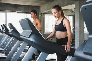 Young couple exercising by running on the treadmill photo
