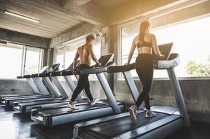 Man and woman exercising by running on the treadmill photo