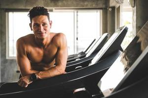 Young handsome man standing near treadmill photo
