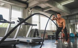 Young man working out with battle ropes at gym photo