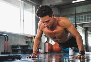 Fitness man doing push up in gym photo
