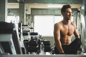A handsome young man standing posing in a gym photo