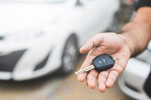 Businessman giving a car key photo