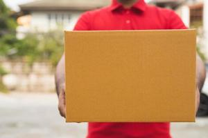 Postman in red uniform holding package photo