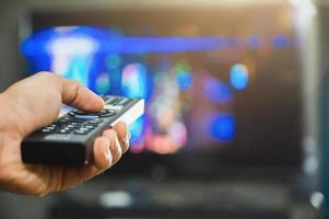 Young man holding television remote control photo