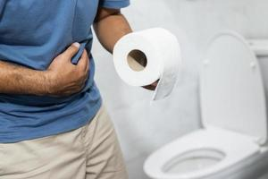 Man in bathroom holding toilet paper photo