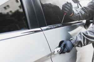 The thief uses a screwdriver to break into a car photo
