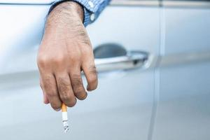 Young man smoking a cigarette in car photo