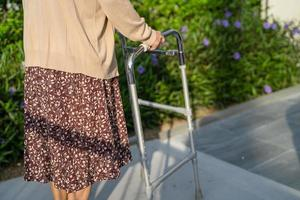 Asian senior or elderly old lady woman patient walk with walker in park with copy space, healthy strong medical concept photo