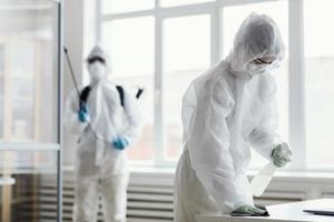 People in protective equipment disinfecting photo