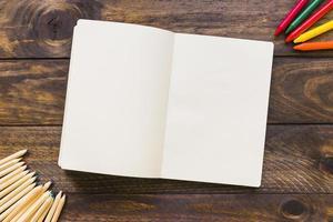 crayones y lápices junto a un cuaderno abierto foto