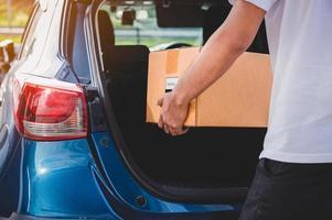 El repartidor está entregando una caja de cartón a los clientes. foto