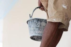 Close up of black paint bucket and painter legs photo
