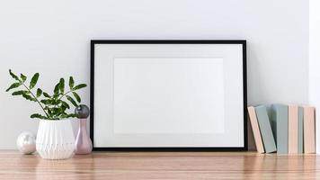 A picture frame on the floor with a flower vase. photo