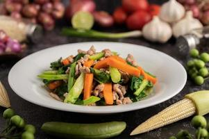 Stir fried kale and carrots with minced pork in a white plate. photo