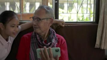 Girl approaching to grandfather watching social online on smartphone. video