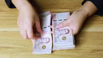 La mano del tirador cuenta el dinero tailandés. video